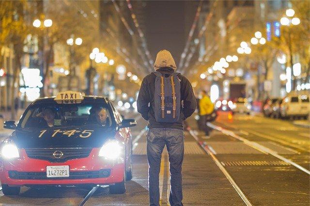 Taxi zastavující pocestnému s batohem na ulici