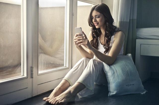 Dívka sedící na posteli, držící v ruce mobil